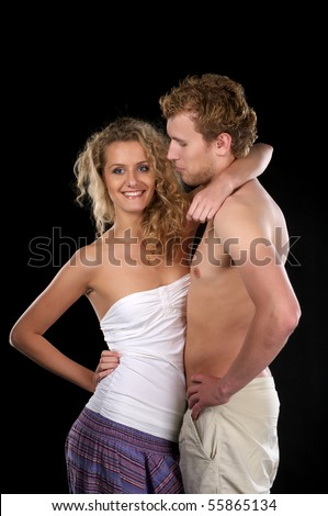 Beautiful woman hugs semi-dressed boyfriend over black background