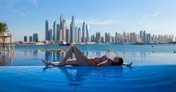 Beautiful woman in a bikini is relaxing on an infinity pool with Dubai view