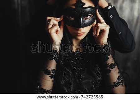beautiful woman in a black dress with a theatrical mask and handsome man ,sexual foreplay concept