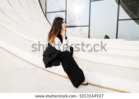 beautiful woman in a black suit posing against the background of the unusual architecture of the city of Baku