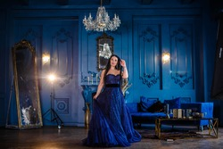 Beautiful woman in a blue ball gown and blue room