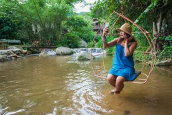 Beautiful woman in a blue dress sits on a swing, taking a happy photo taking a selfie surrounded by waterfalls and green trees.