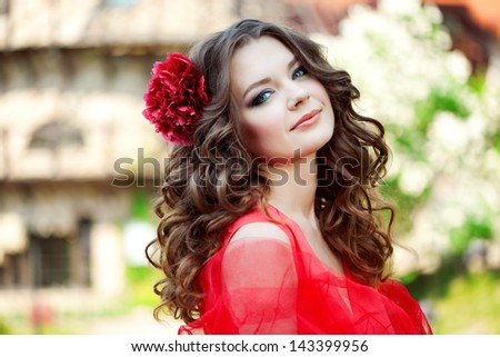 Beautiful woman in a bright red dress on a background of the mill