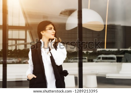 beautiful woman in a business suit against the background of a large window
