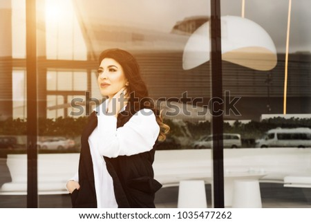 beautiful woman in a business suit against the background of large windows