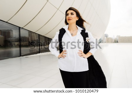 beautiful woman in a business suit posing against the background of large windows