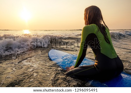 Beautiful woman in a diving suit for swimming surfing in the Indian Ocean on the background sunset sky and waves.professional surfer girl in a wetsuit doing sports at sea.extreme, adrenaline and youth #1296095491