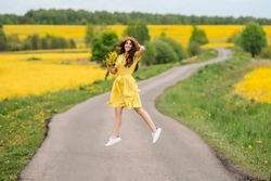 beautiful woman in a dress and hat with a bouquet of yellow flowers walking on the road in the fields of rapeseed. jumping having fun outdoors on the road. the concept of freedom.