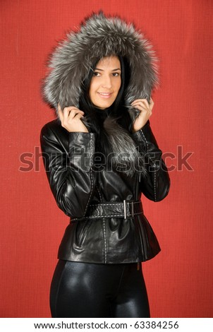 beautiful woman in a fur coat on a red background
