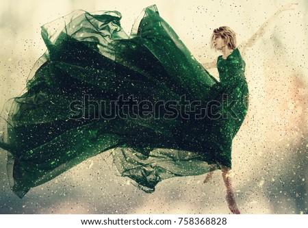 Beautiful woman in a green dress jumping