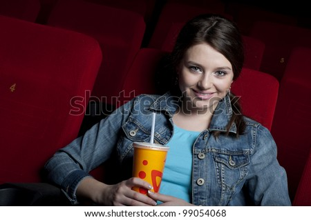 beautiful woman in a movie theater, watching a movie and drink a drink