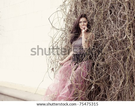 beautiful woman in a pink skirt fashion in the branches of trees