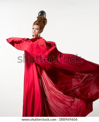 Beautiful woman in a silk red fabric on the white background