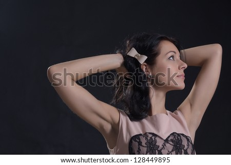 Beautiful woman in a stylish dress with a bow in her hair standing with her hands clasped behind her head looking upwards lost in thought