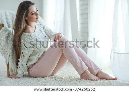 Beautiful woman in a sweater at home #374260252