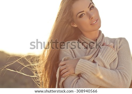 Beautiful woman in a sweater in the fall.Warm light sunset