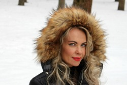 Beautiful woman in a warm jacket with a fur hood in a winter park.