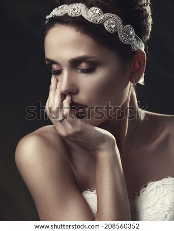 Beautiful woman in a white dress in the image of a bride with a sad face. Hand touching face. Instagramm style.