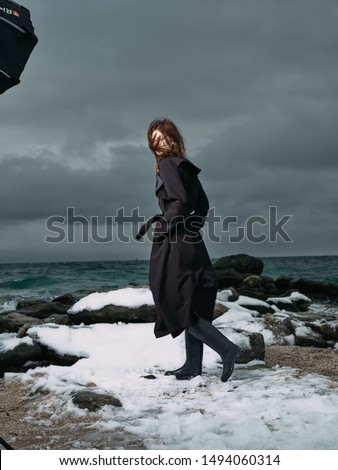 Beautiful woman in a white snow coat travel winter mountains ocean sea
