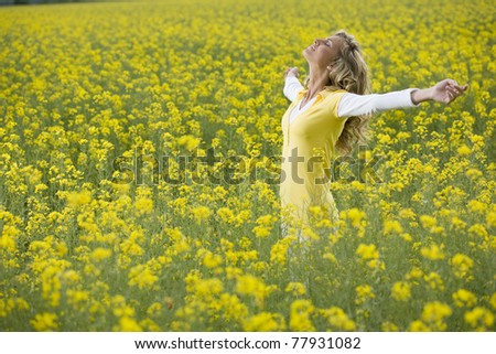 Beautiful woman in a yellow flowers field with arms outstretched