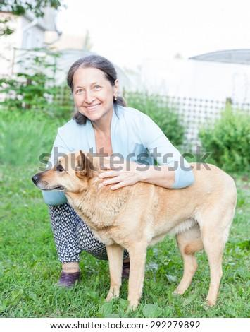 Beautiful woman in   age of   dog on   lawn.
