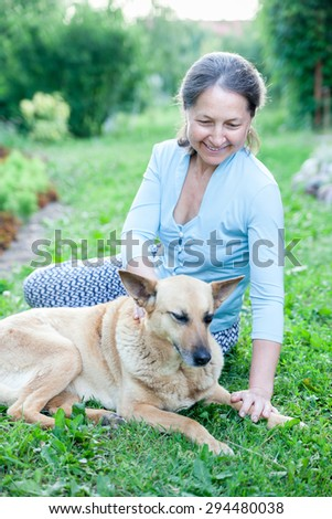 Beautiful woman in   age with   dog on   lawn.