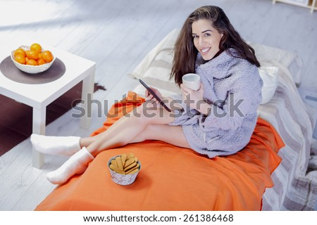 Beautiful woman in bed having coffee, tablet, laptop, computer, phone laughing