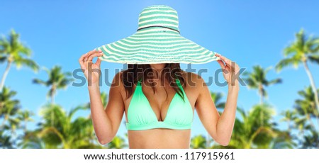 Beautiful woman in bikini and a hat. Exotic luxury resort.