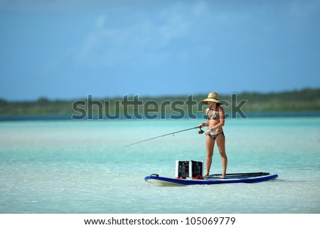 Beautiful woman in bikini fishing and paddleboarding in the bahamas