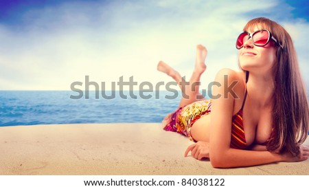 Beautiful woman in bikini sunbathing at the seaside