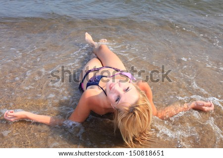 Beautiful woman in bikini sunbathing at the seaside blue sky