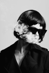 beautiful woman in black coat and sunglasses blows smoke