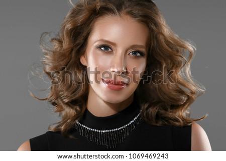 41ad538548 Beautiful woman in black dress elegant over gray background. Studio shot.   1069469243