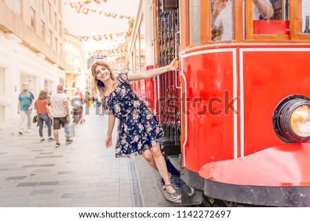 Beautiful woman in black dress hangs at nostalgic Istiklal tramway at istiklal street,Istanbul,Turkey - Shutterstock ID 1142272697