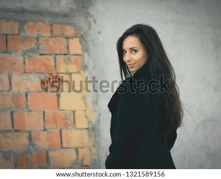 Beautiful woman in black near the brickwall. Fashion shot. #1321589156