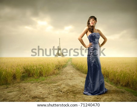 Beautiful woman in blue dress with Eiffel Tower on the background