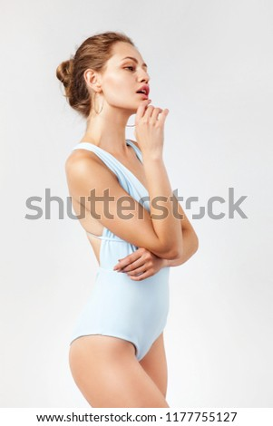 Beautiful woman in blue monokini against white background #1177755127