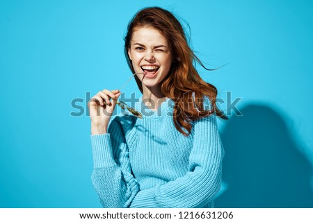 beautiful woman in blue sweater holding glasses in her hands