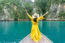 Beautiful woman in bright yellow dress, wearing hat with a black bow, standing on a local long tail boat and raising both arms, enjoys the beauty of Phi Phi Island, Krabi, Thailand.