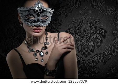 Beautiful woman in carnival mask on dark vintage background. Space for text.