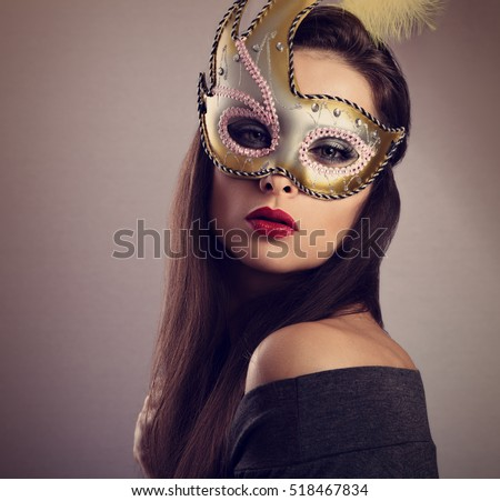 Stock Photo Beautiful woman in carnival mask with bright makeup and red lipstick. Closeup toned portrait