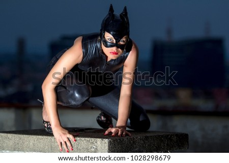 Beautiful woman in catwoman leather latex on the roof