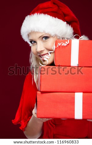 Beautiful woman in Christmas cap holds a set of presents, isolated on purple