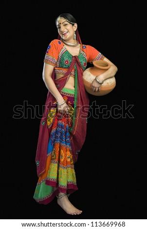 Beautiful woman in colorful lehenga choli carrying water pot