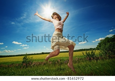 Beautiful woman in cowboy hat jumping.