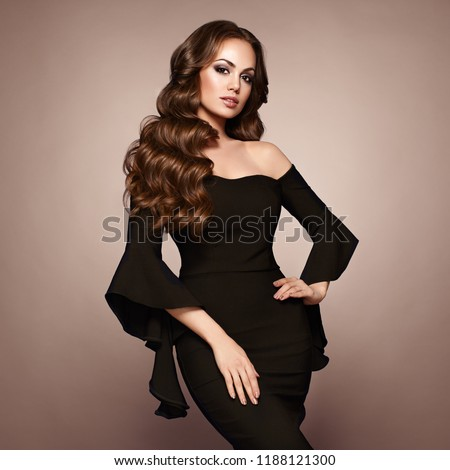 Beautiful woman in elegant black evening dress. Brunette Girl with Long Healthy and Shiny Curly Hair. Care and Beauty. Beautiful Model Woman with Wavy Hairstyle