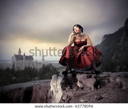 Beautiful woman in elegant dress with fabulous castle on the background