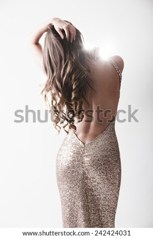 Beautiful woman in elegant expensive evening shiny dress with naked rear