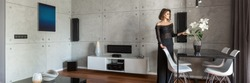 Beautiful woman in elegant living room with concrete wall and black table, panorama