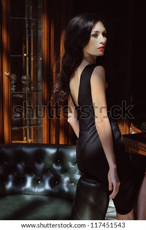 beautiful woman in evening dress sitting on a leather armchair in a luxurious interior